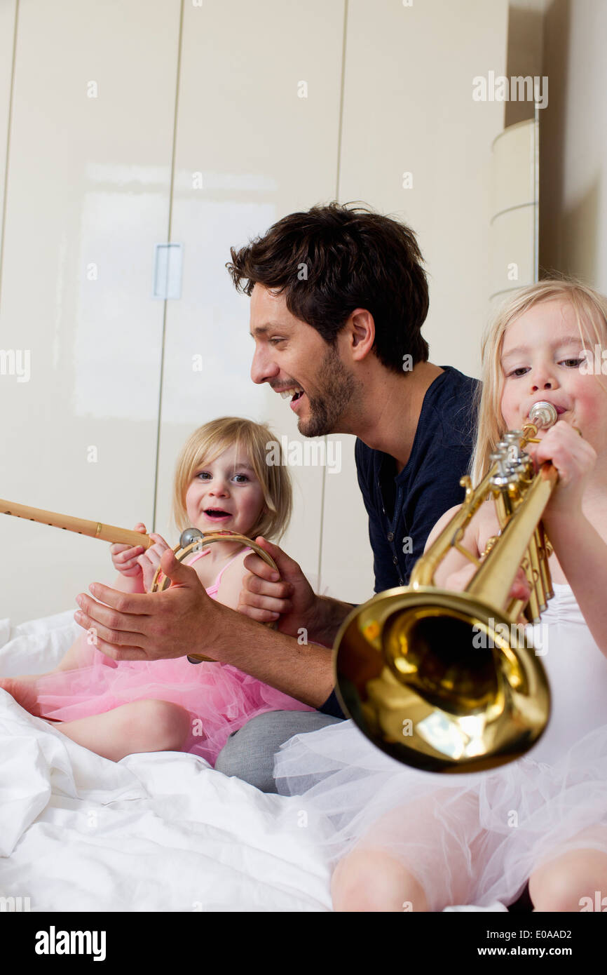Father and two young daughters playing music - Stock Image