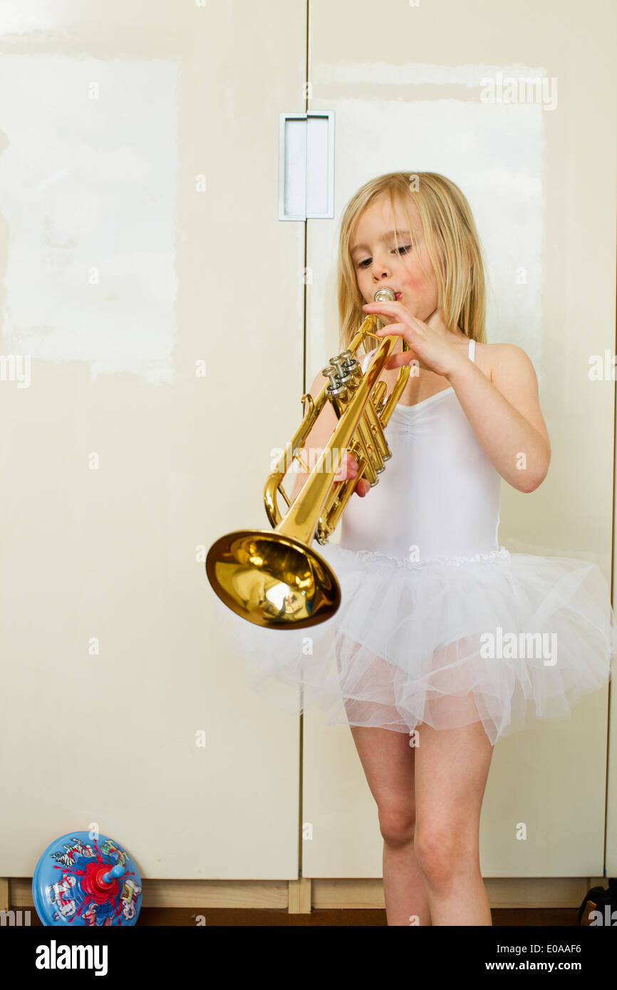 Portrait of young girl playing the trumpet - Stock Image