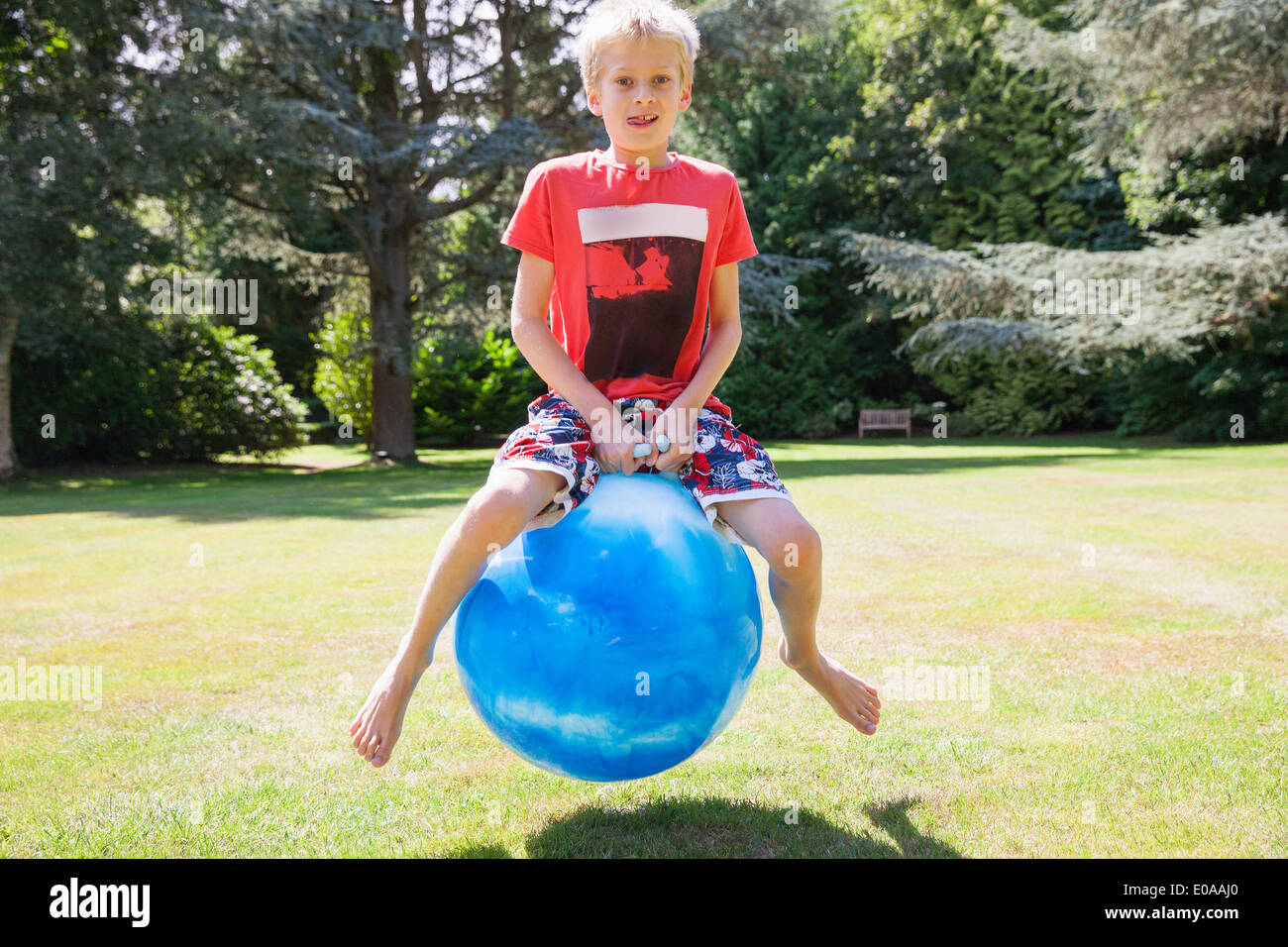 Boy jumping on space hopper - Stock Image