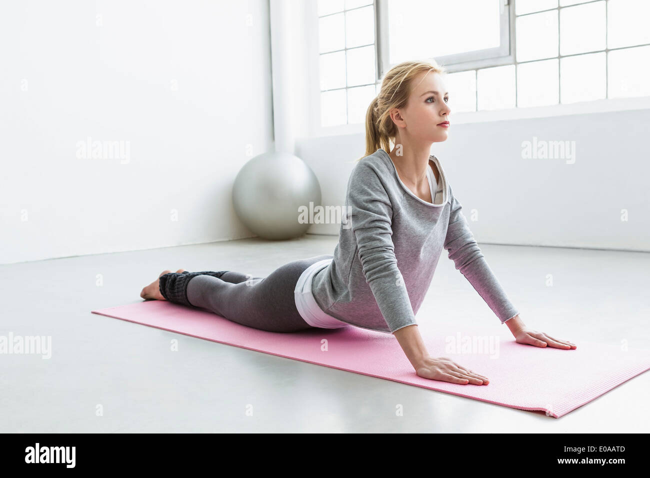 Young woman in yoga pose on yoga mat - Stock Image