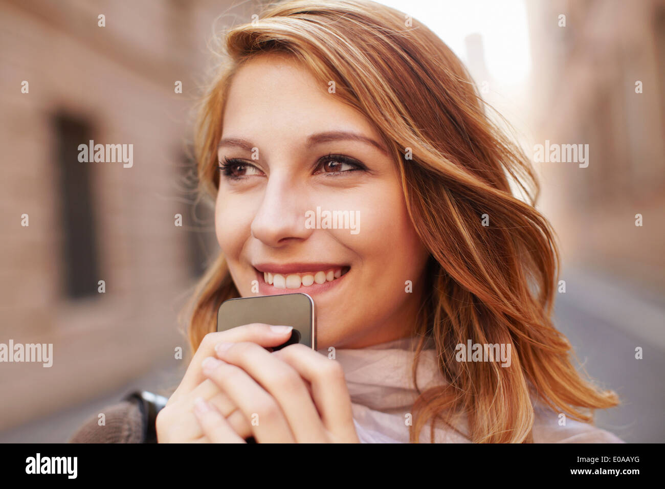 Close up of attractive young woman with smartphone - Stock Image