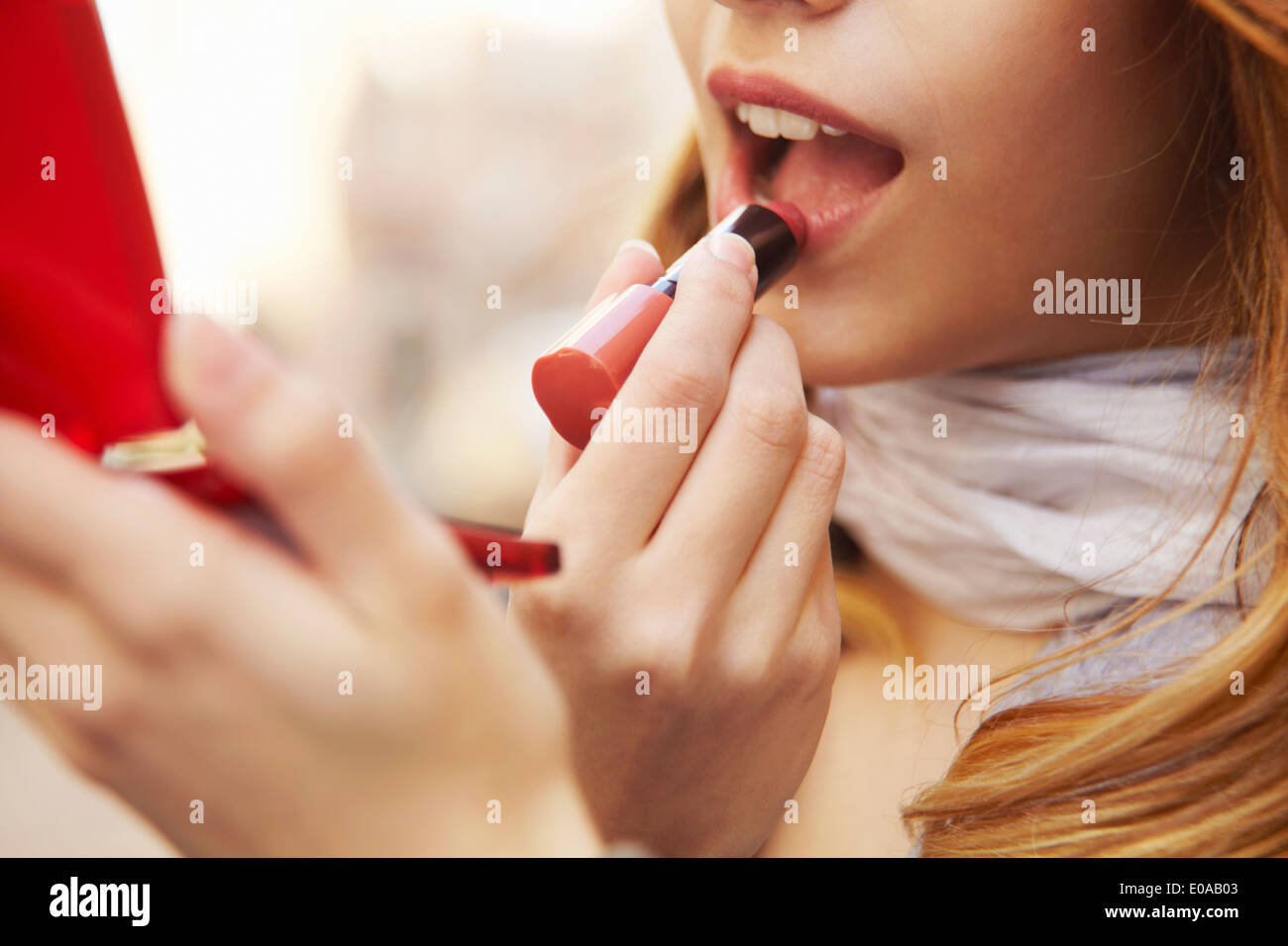Close up of young woman putting on lipstick - Stock Image