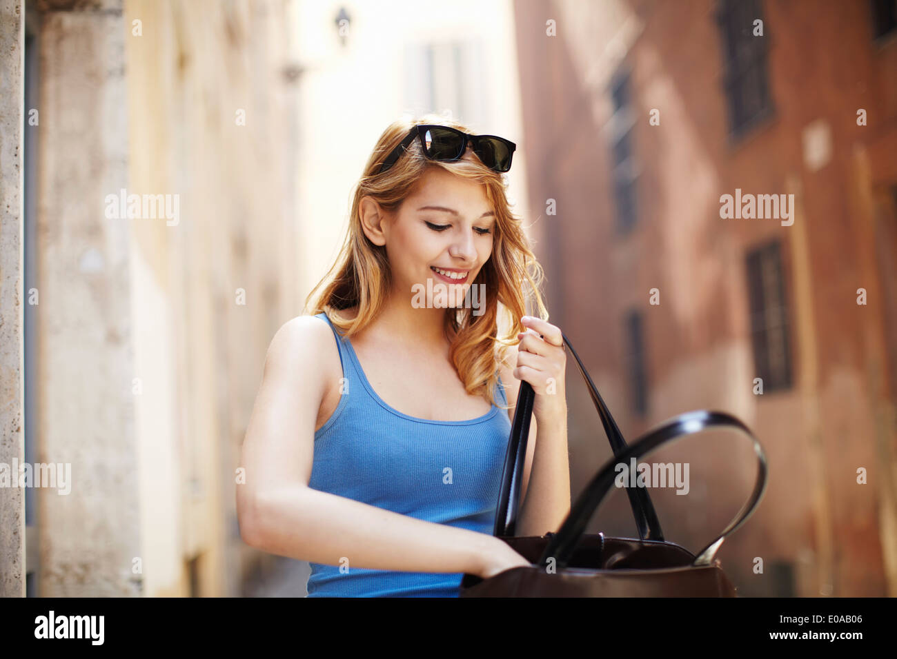 Young woman searching in shoulder bag, Rome, Italy Stock Photo