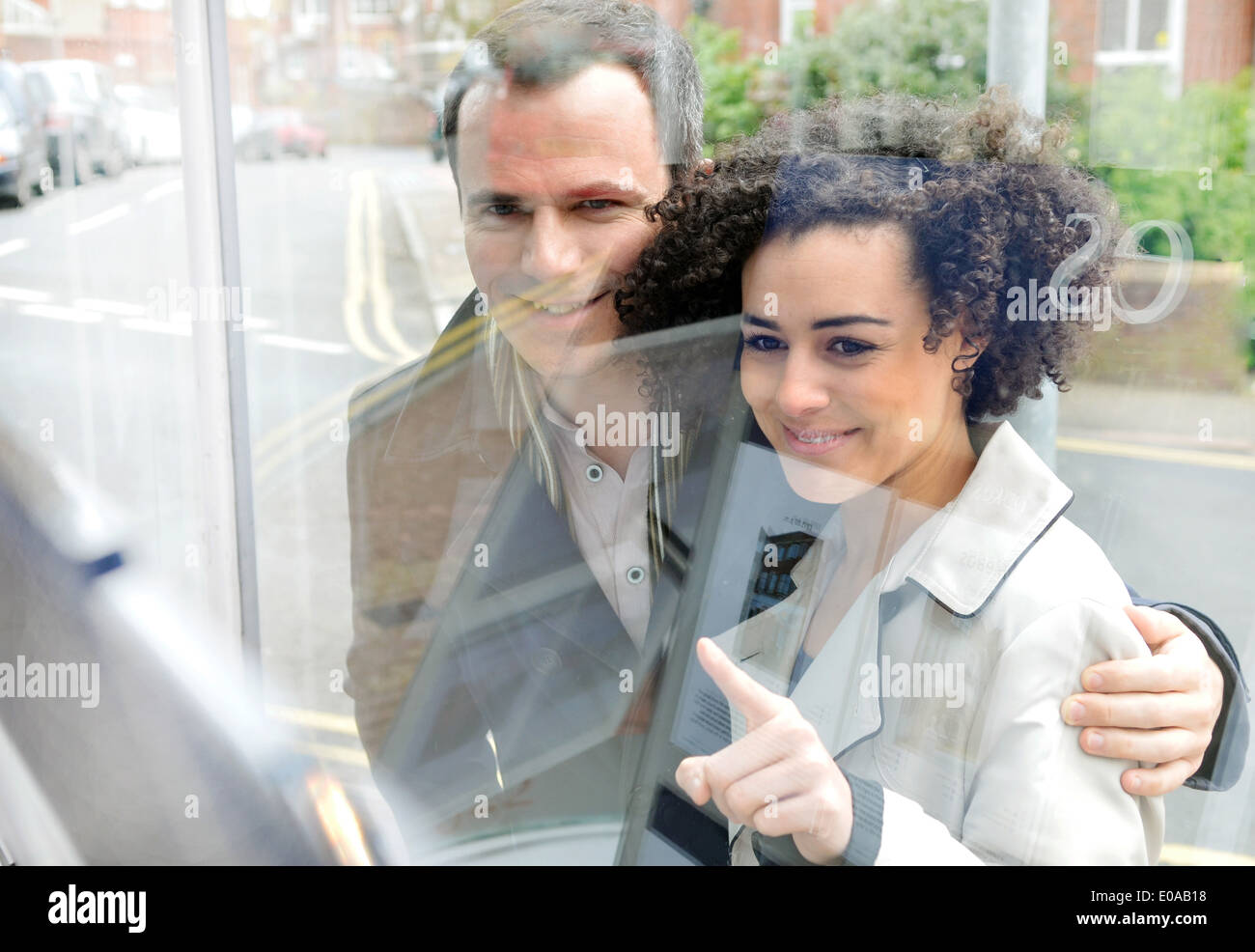 Couple window shopping, young woman pointing - Stock Image