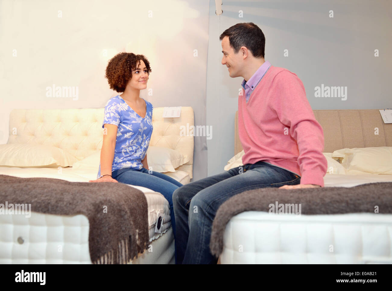 Couple sitting on beds in furniture shop showroom - Stock Image