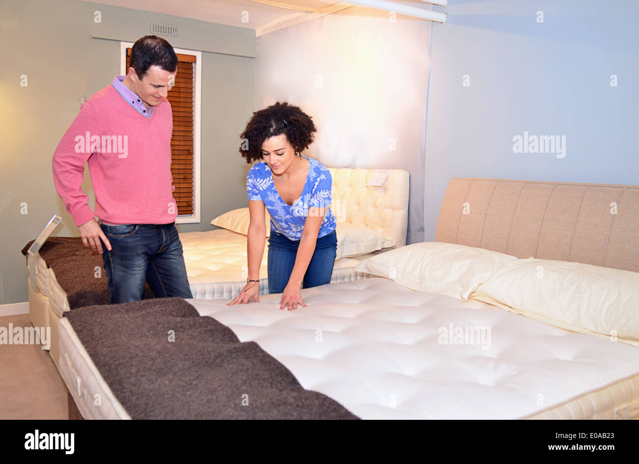 Couple testing beds in furniture shop showroom - Stock Image