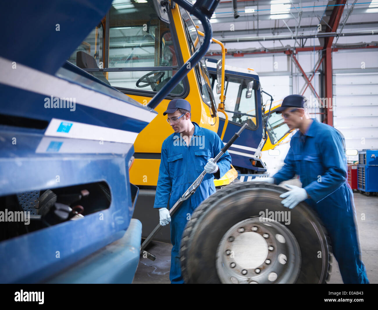 Engineers prepare to fix wheel in truck repair factory - Stock Image