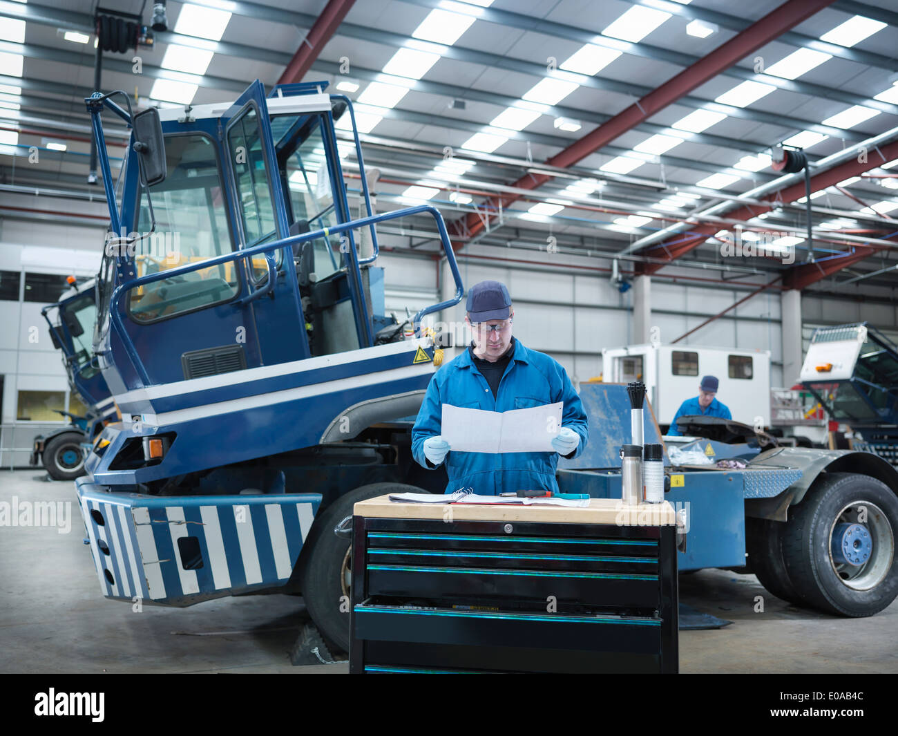 Engineer working from plans in truck repair factory - Stock Image
