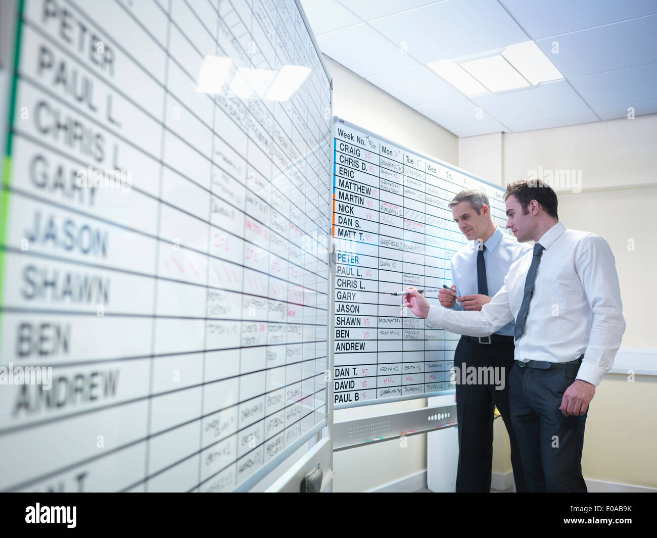 Managers writing notes on board in office - Stock Image