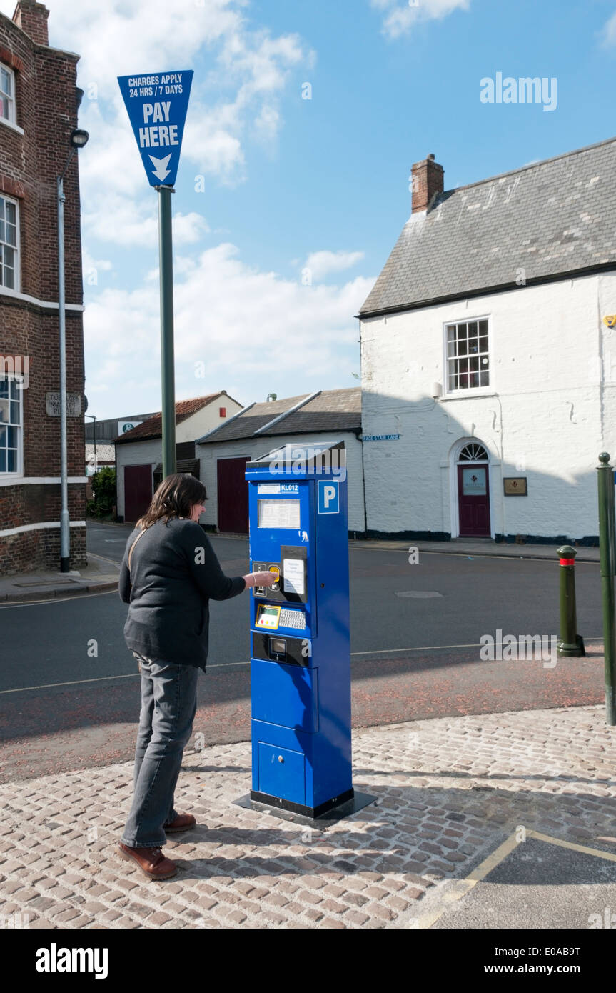 Woman purchasing a car park ticket from a machine on the Tuesday Market Place, King's Lynn, Norfolk. - Stock Image