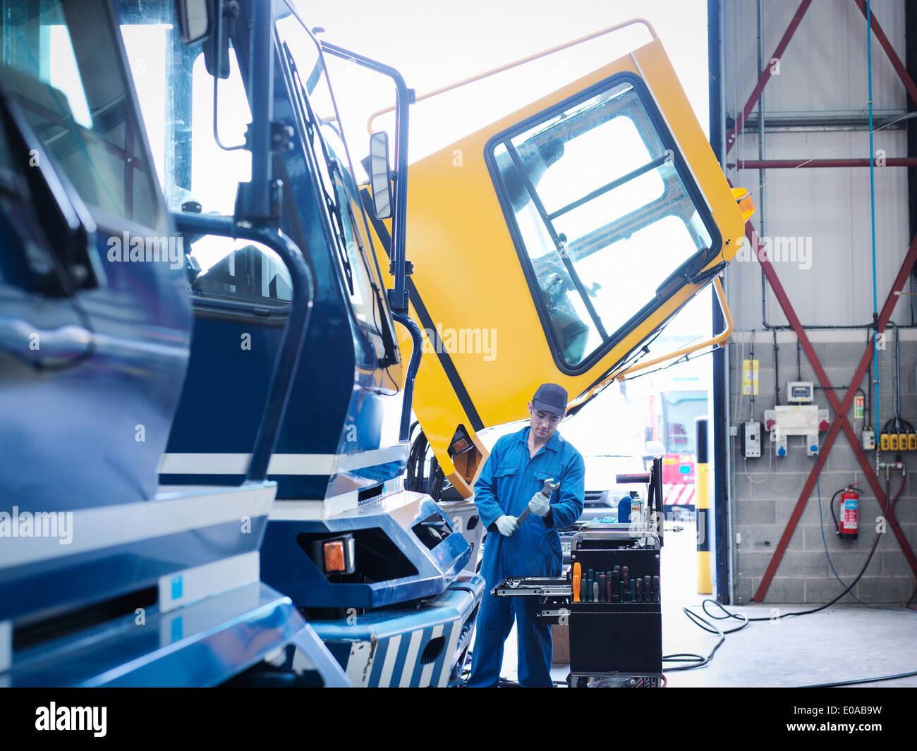 Engineer working on engine in truck repair factory - Stock Image