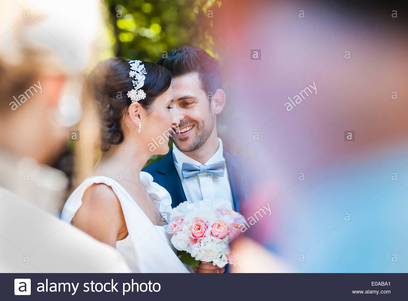 Mid adult bride and groom surrounded by wedding guests - Stock Image