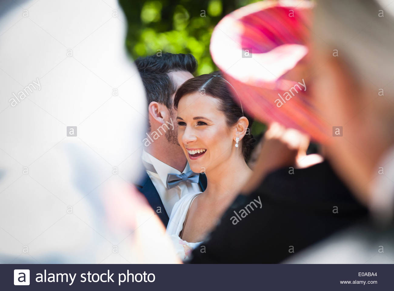 Mid adult bride and groom surrounded by guests Stock Photo