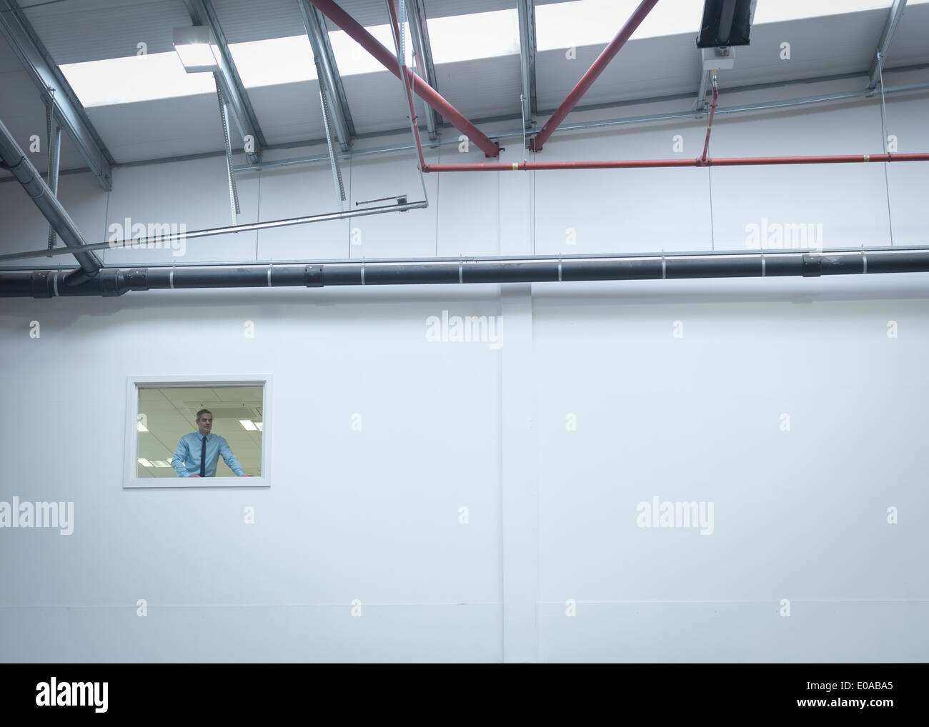Manager inspecting truck repair factory from office window - Stock Image