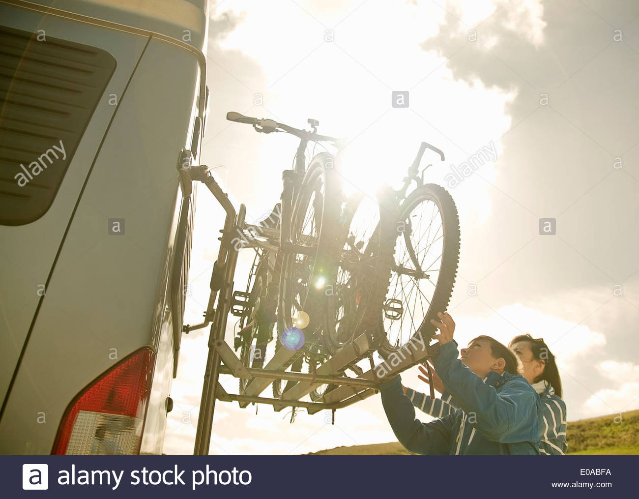 Mother and son stacking bikes on back of camper van Stock Photo
