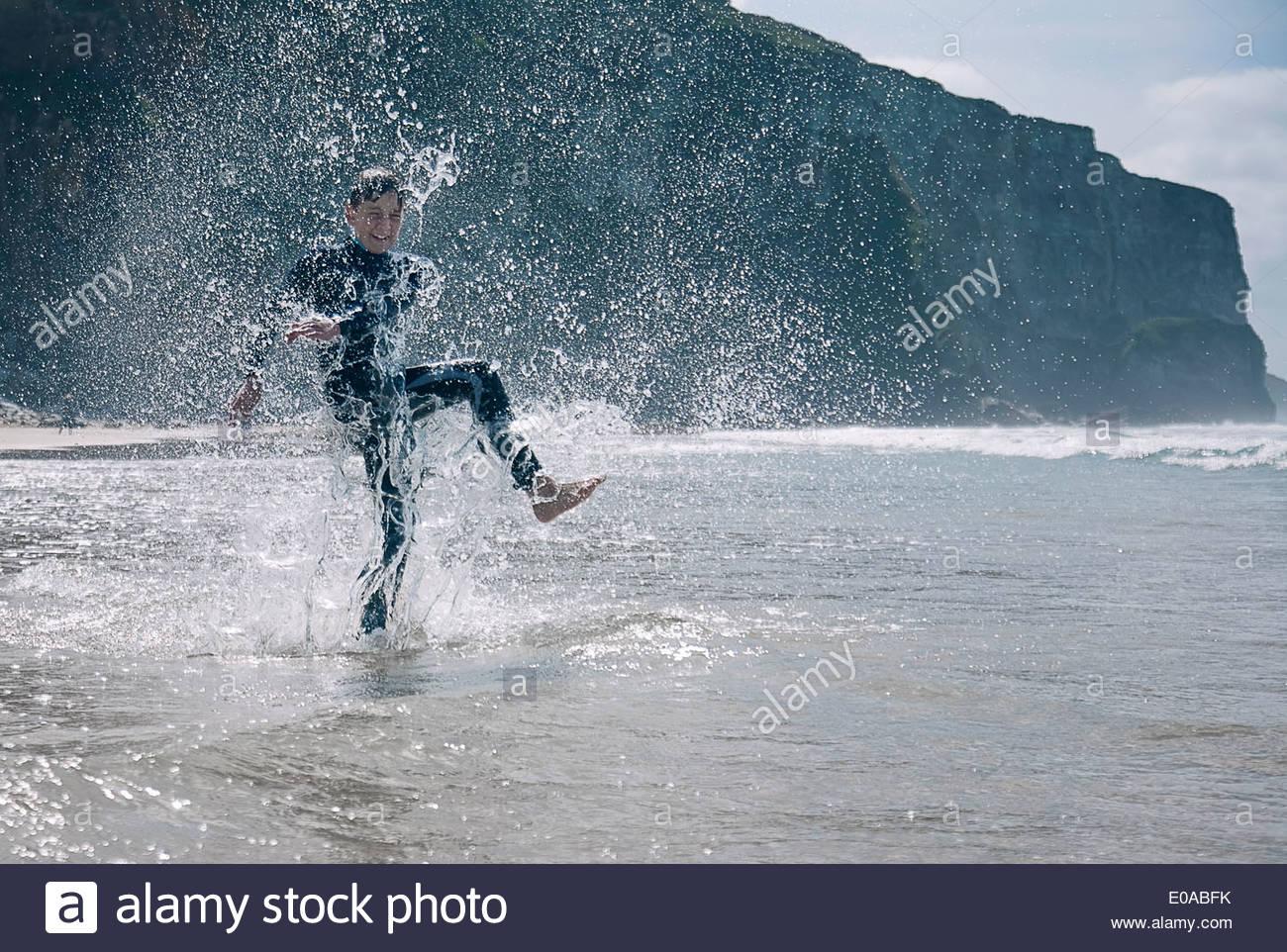 Boy wearing wetsuit, splashing in sea - Stock Image