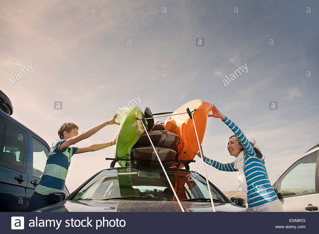 Mother and son stacking kayaks on top of car - Stock Image