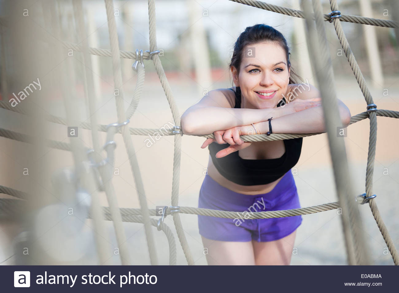 Young woman leaning against rope Stock Photo