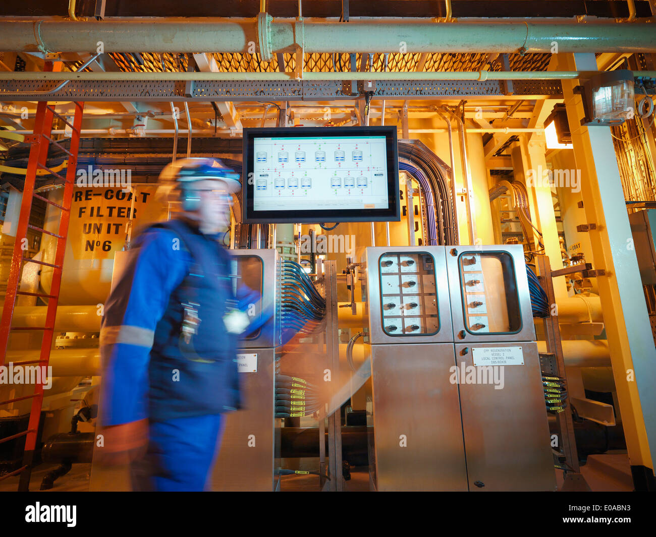 Engineer passing digital display in power station - Stock Image
