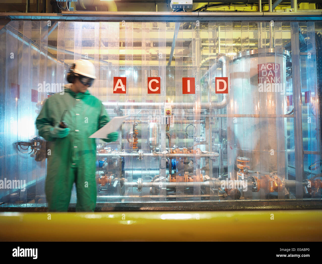 Engineer reading notes in acid store in power station - Stock Image