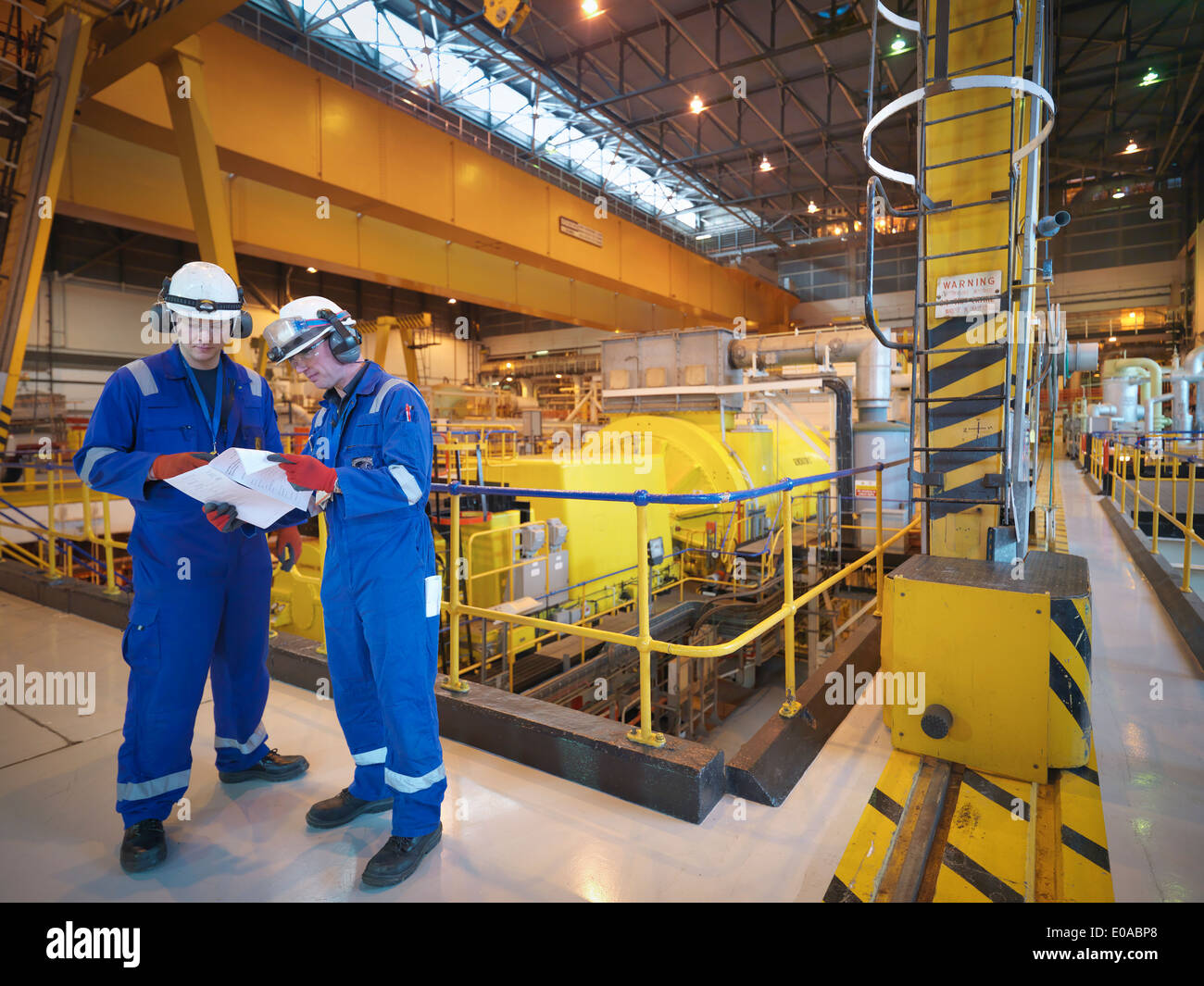Workers reading notes in turbine hall of power station - Stock Image