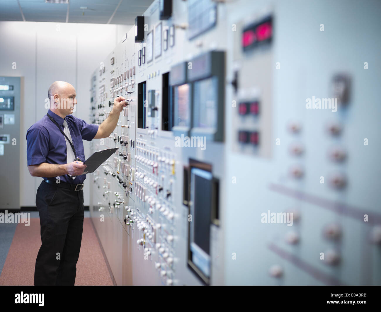 Engineer inspecting nuclear power station control room simulator - Stock Image