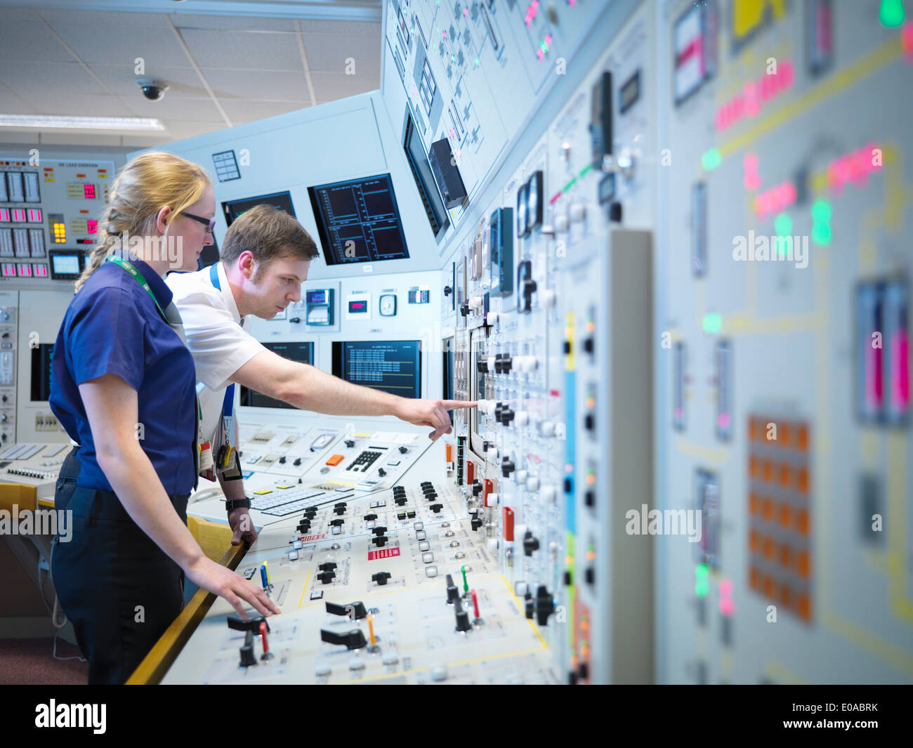 Female operator and trainee in nuclear power station control room simulator - Stock Image