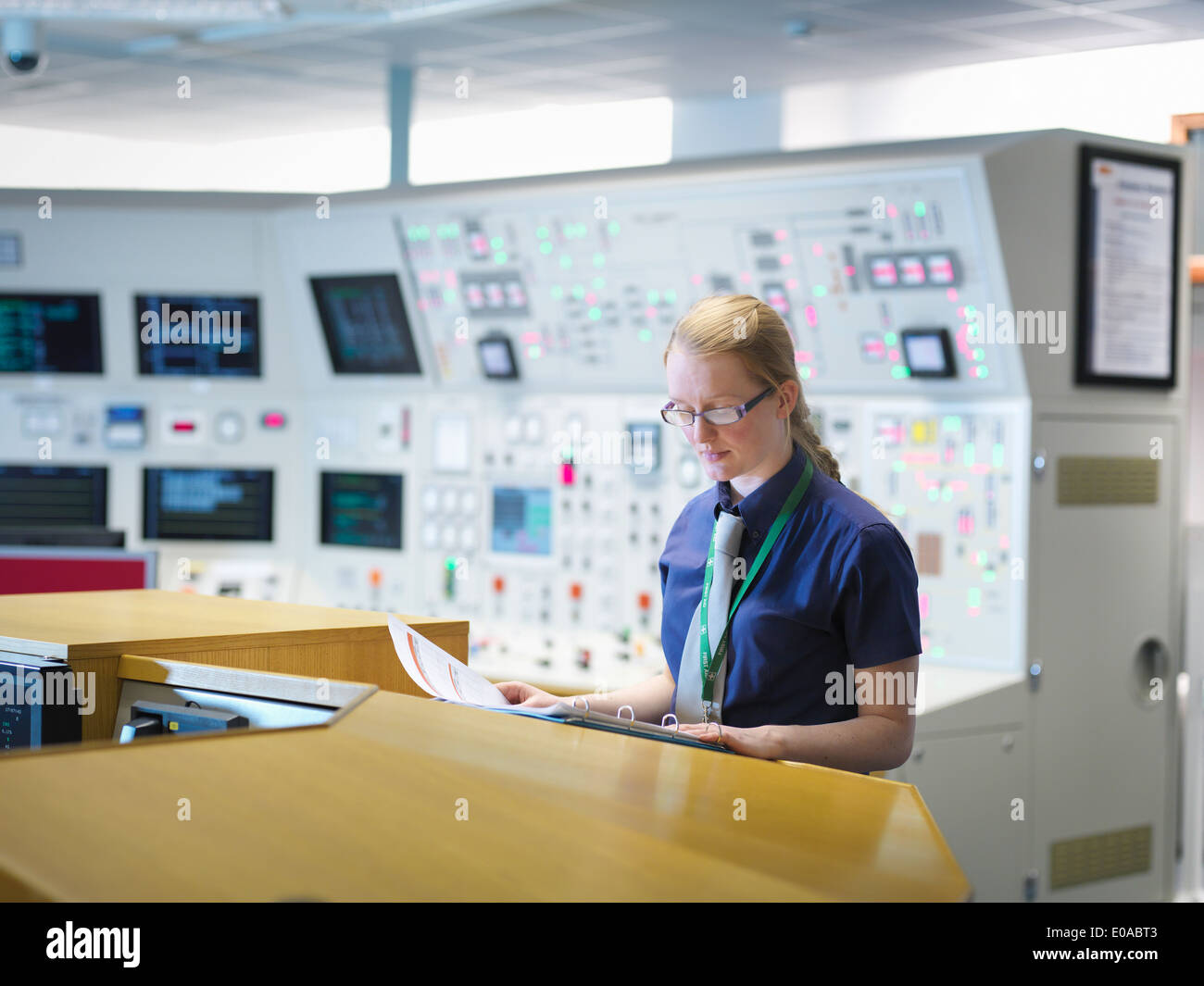Female operator reading notes in nuclear power station control room simulator - Stock Image
