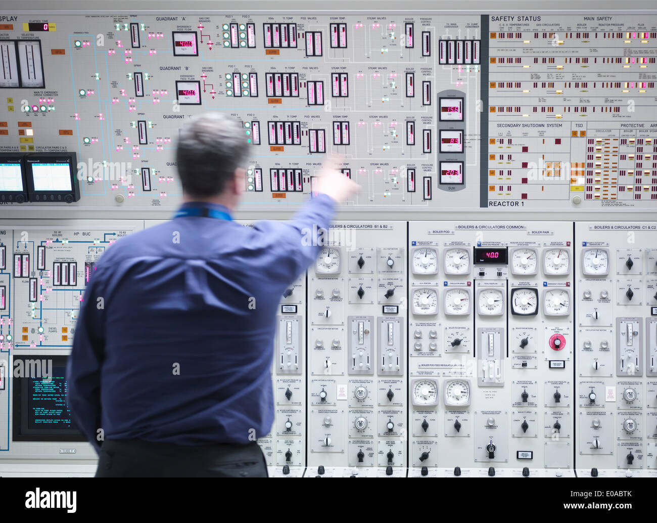 Operator adjusting controls in nuclear power station control room simulator - Stock Image