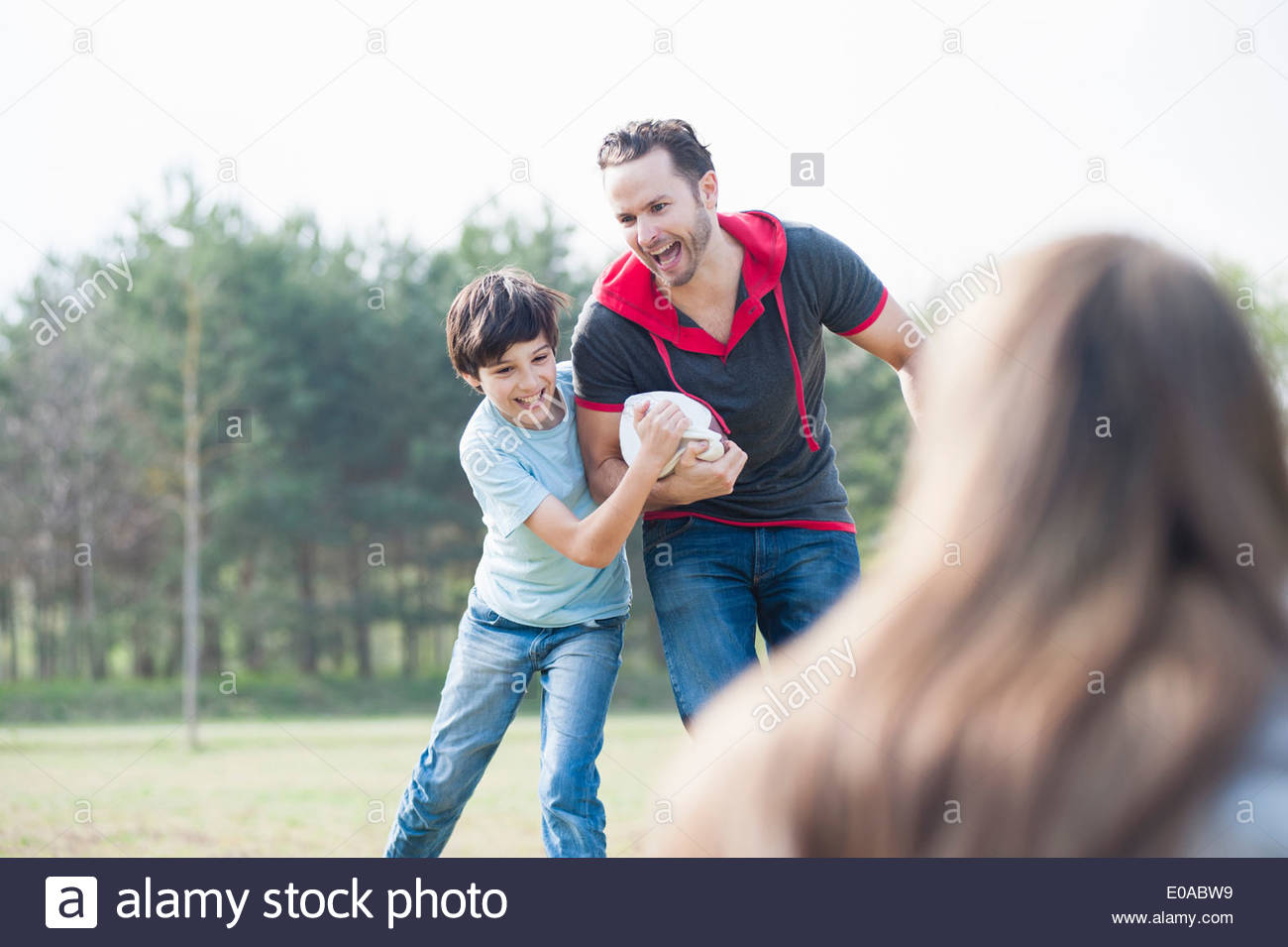 Father and son practicing rugby tackle in park - Stock Image