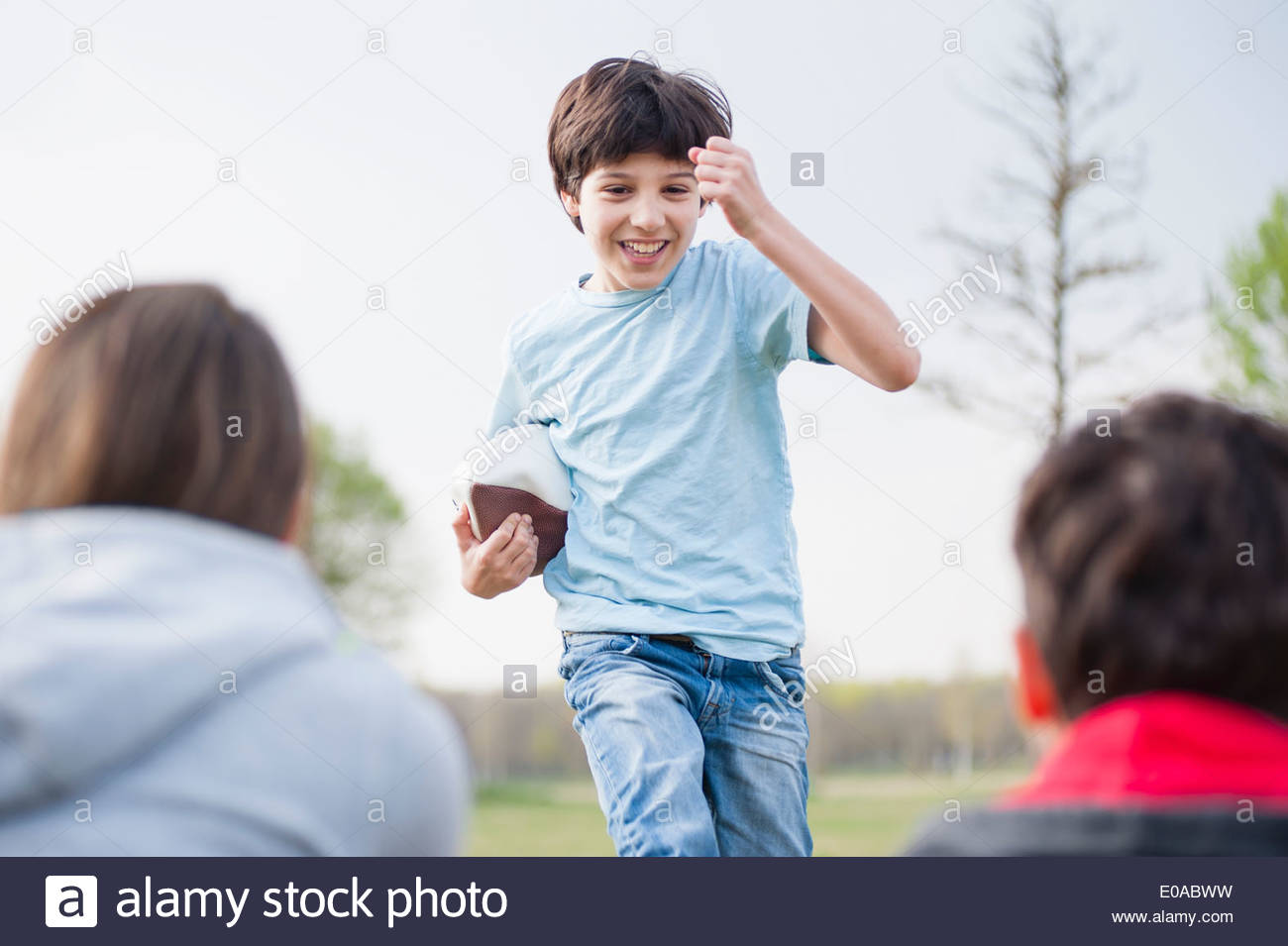 Parents watching son run with rugby ball in park - Stock Image