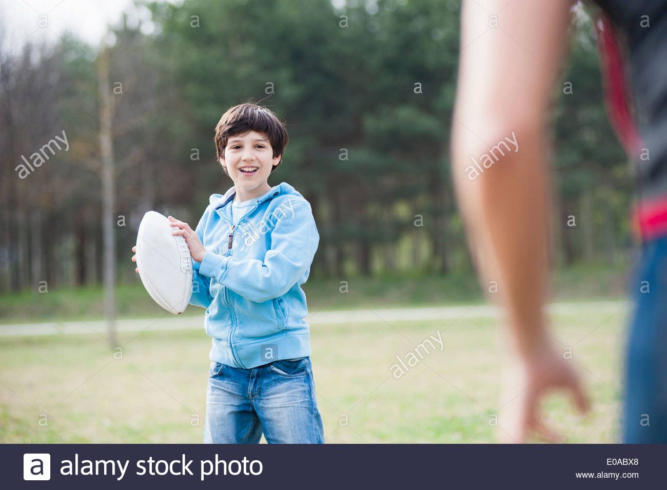 Boy practicing rugby ball throw with his father in park - Stock Image