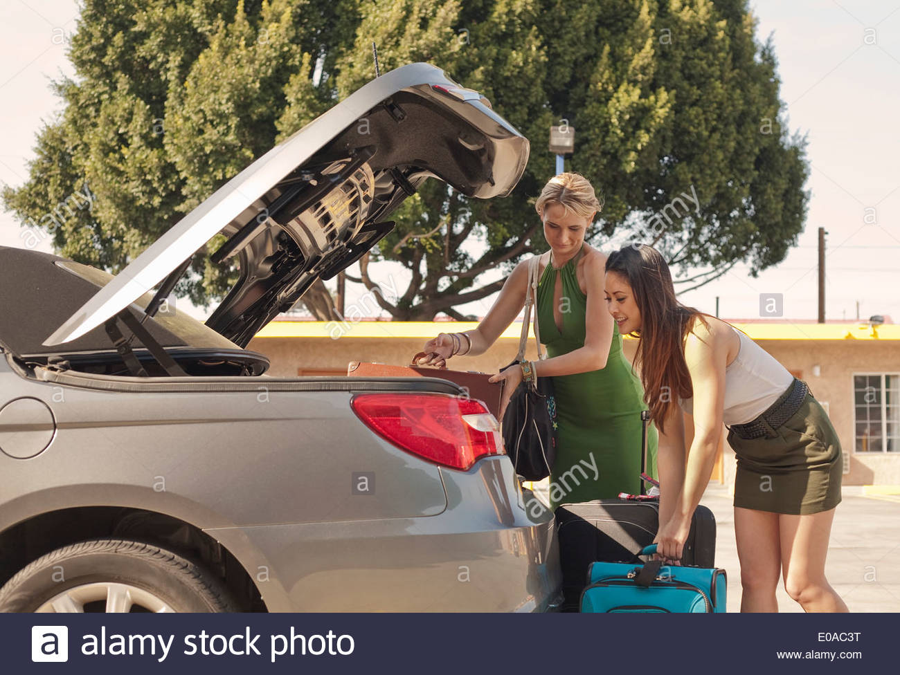 Young women putting suitcases into car - Stock Image