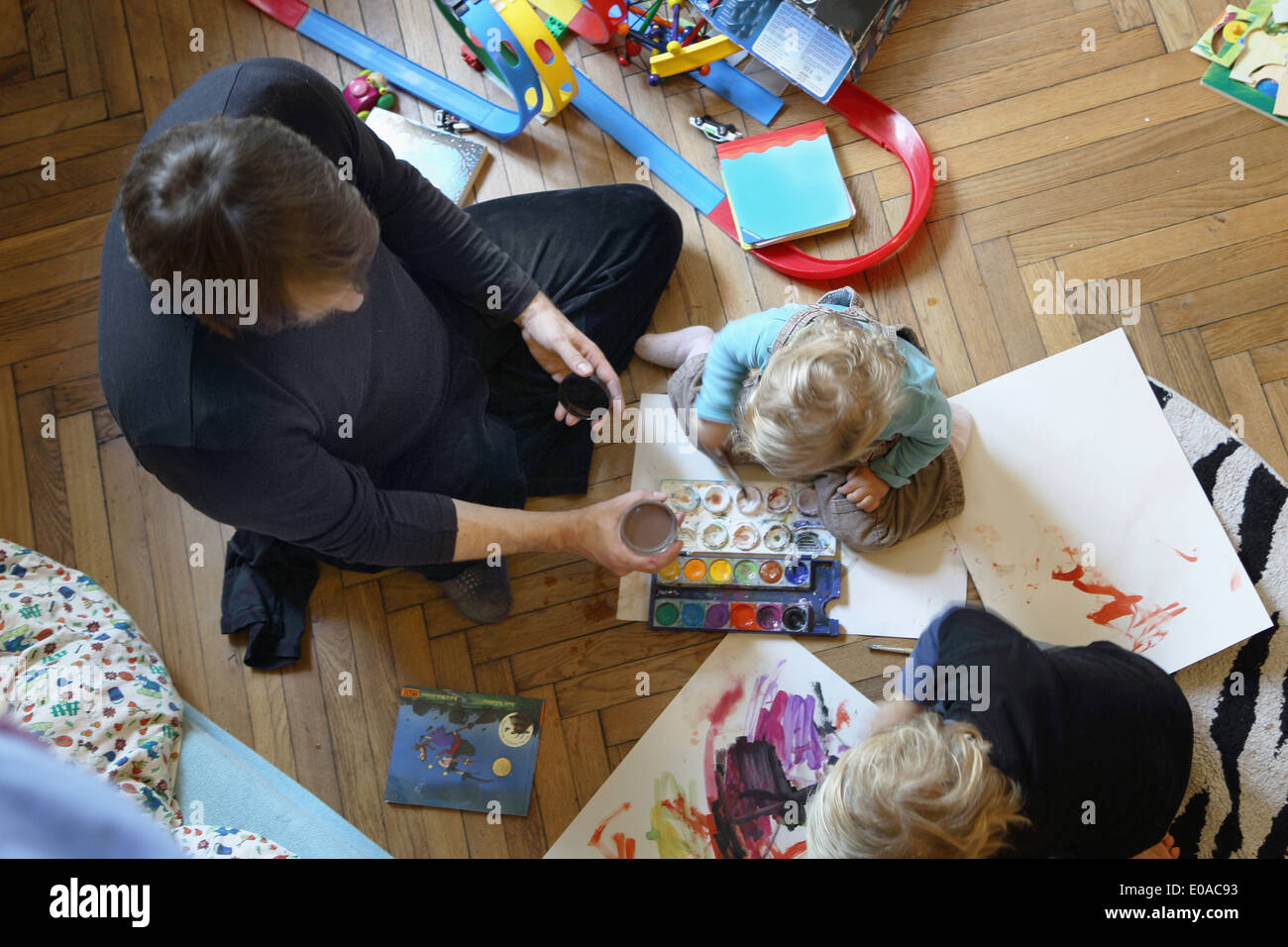 Father and sons painting on floor - Stock Image