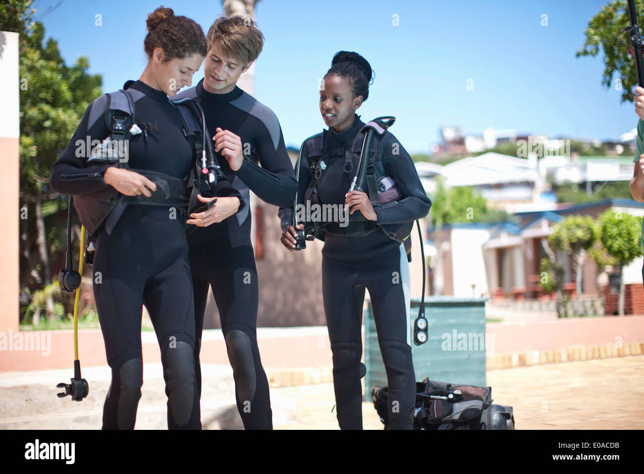 Scuba diving instructor strapping equipment onto pupil - Stock Image
