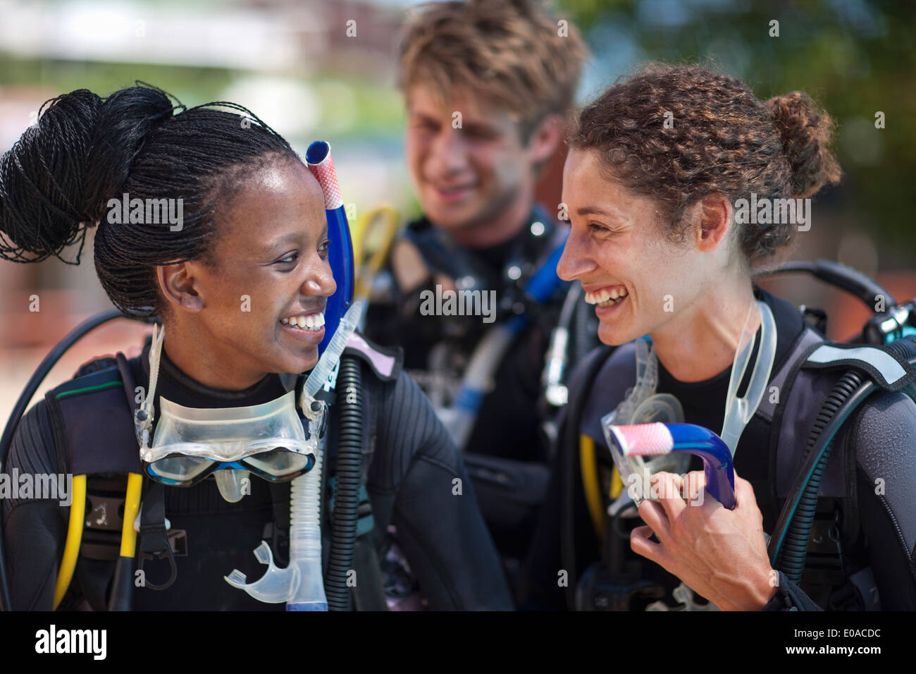 Three young adult scuba divers preparing for pool practice - Stock Image