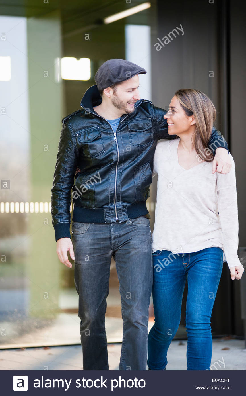 Mid adult couple, man with arm around woman - Stock Image