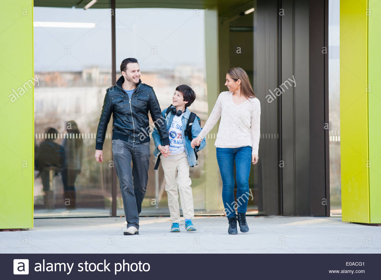 Family with one son walking outside building - Stock Image