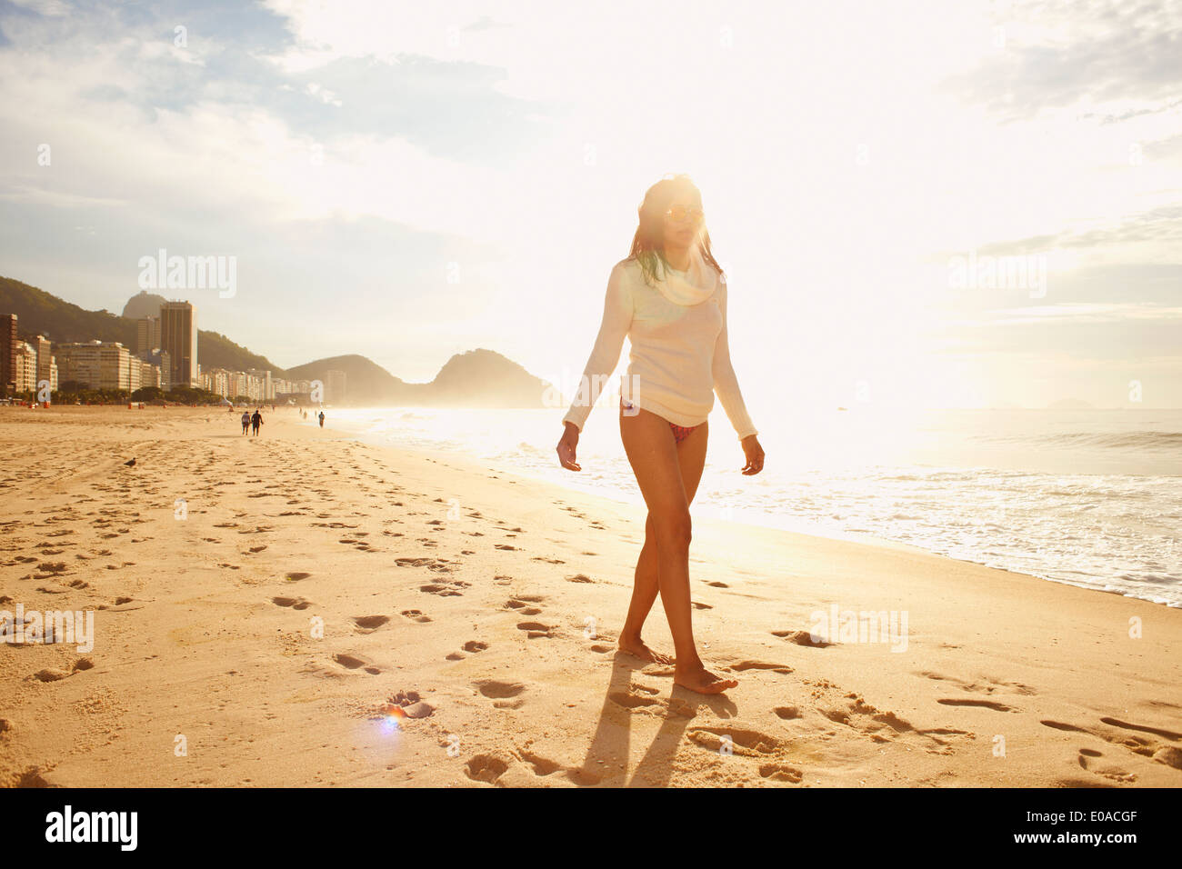 Mature woman strolling on sunlit Copacabana beach, Rio De Janeiro, Brazil - Stock Image