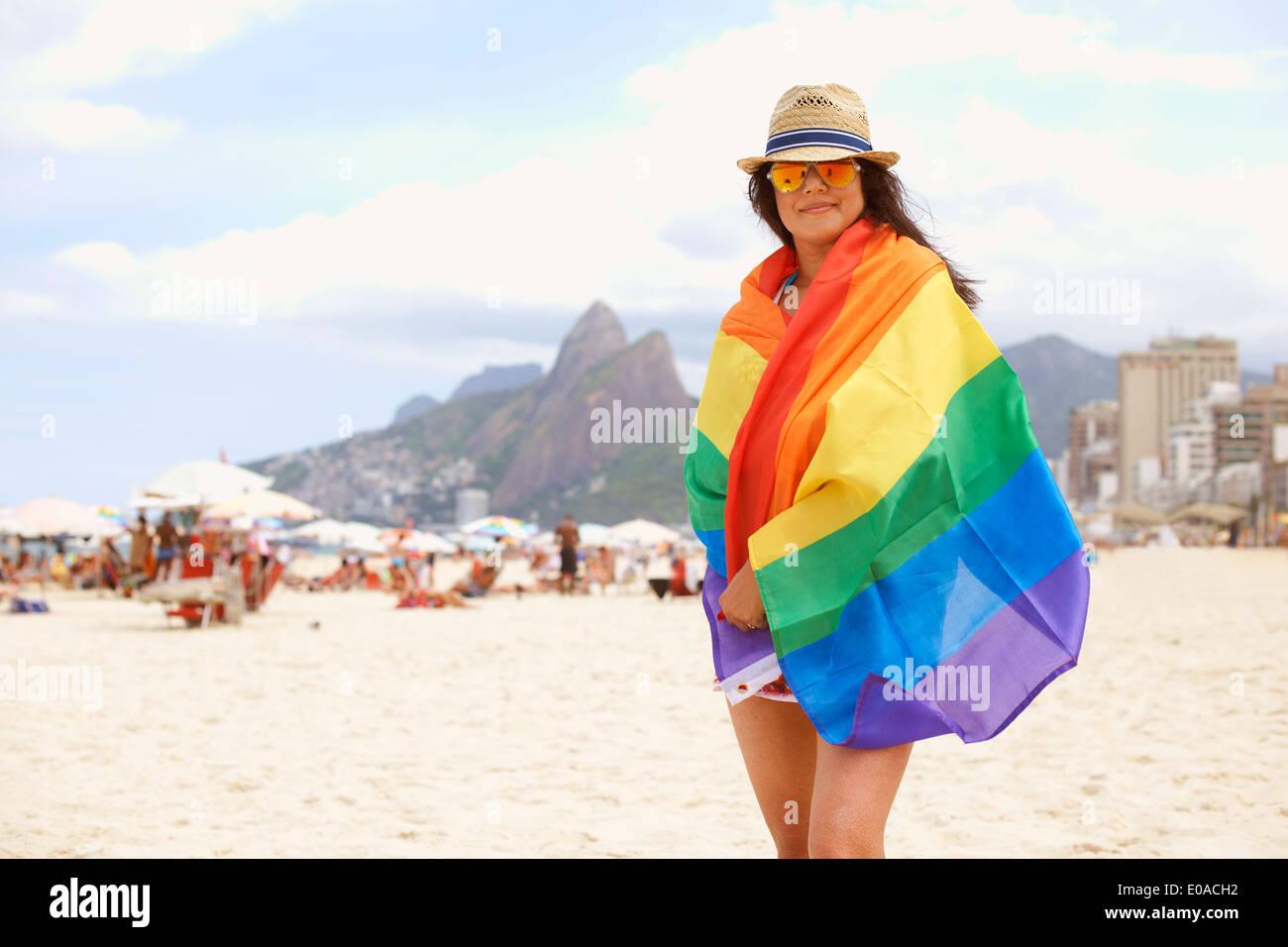 Portrait of mature woman wrapped in multicolored flag, Ipanema beach, Rio De Janeiro, Brazil - Stock Image