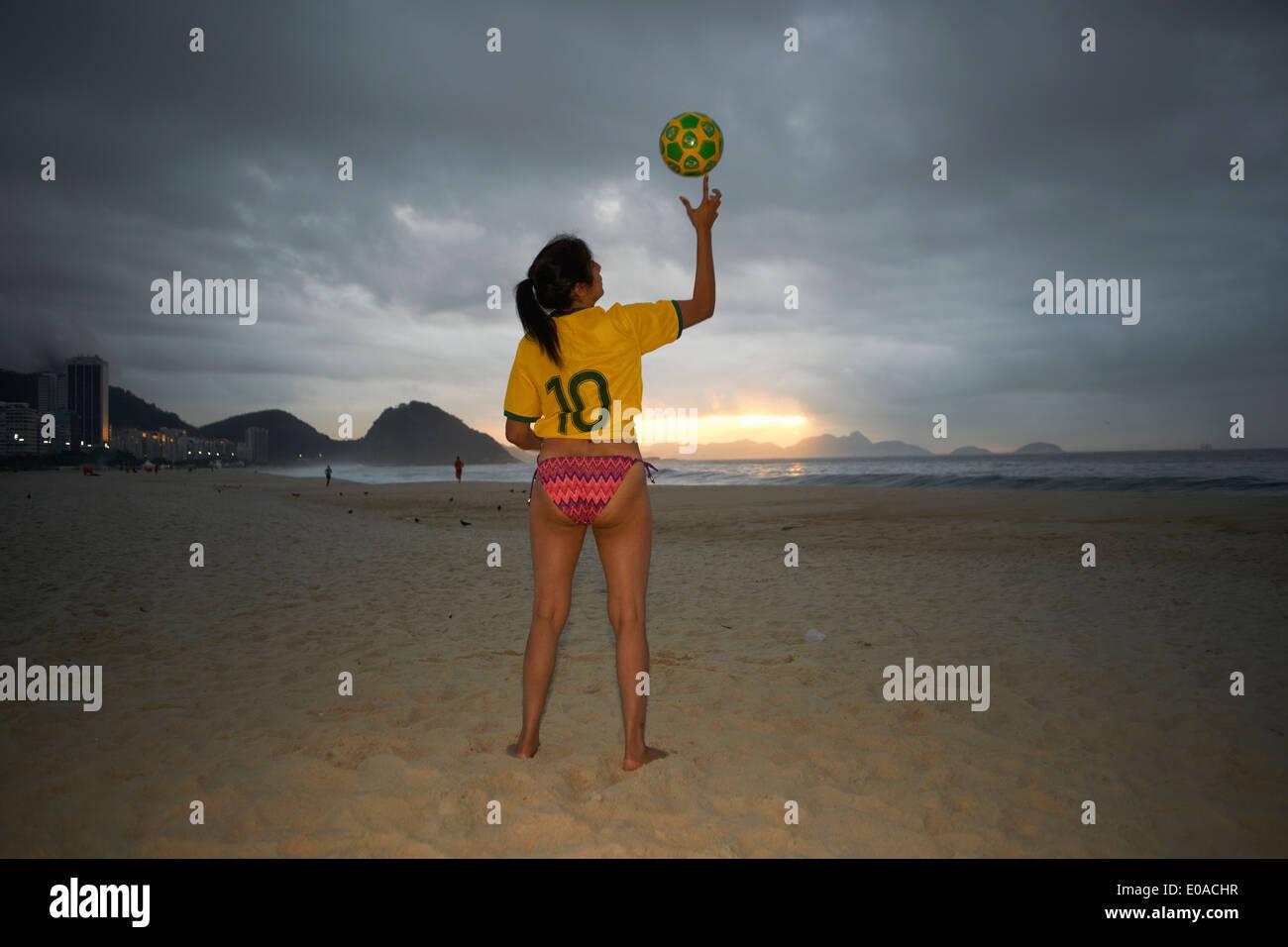 Mature woman balancing soccer ball on finger, Copacabana beach, Rio De Janeiro, Brazil - Stock Image