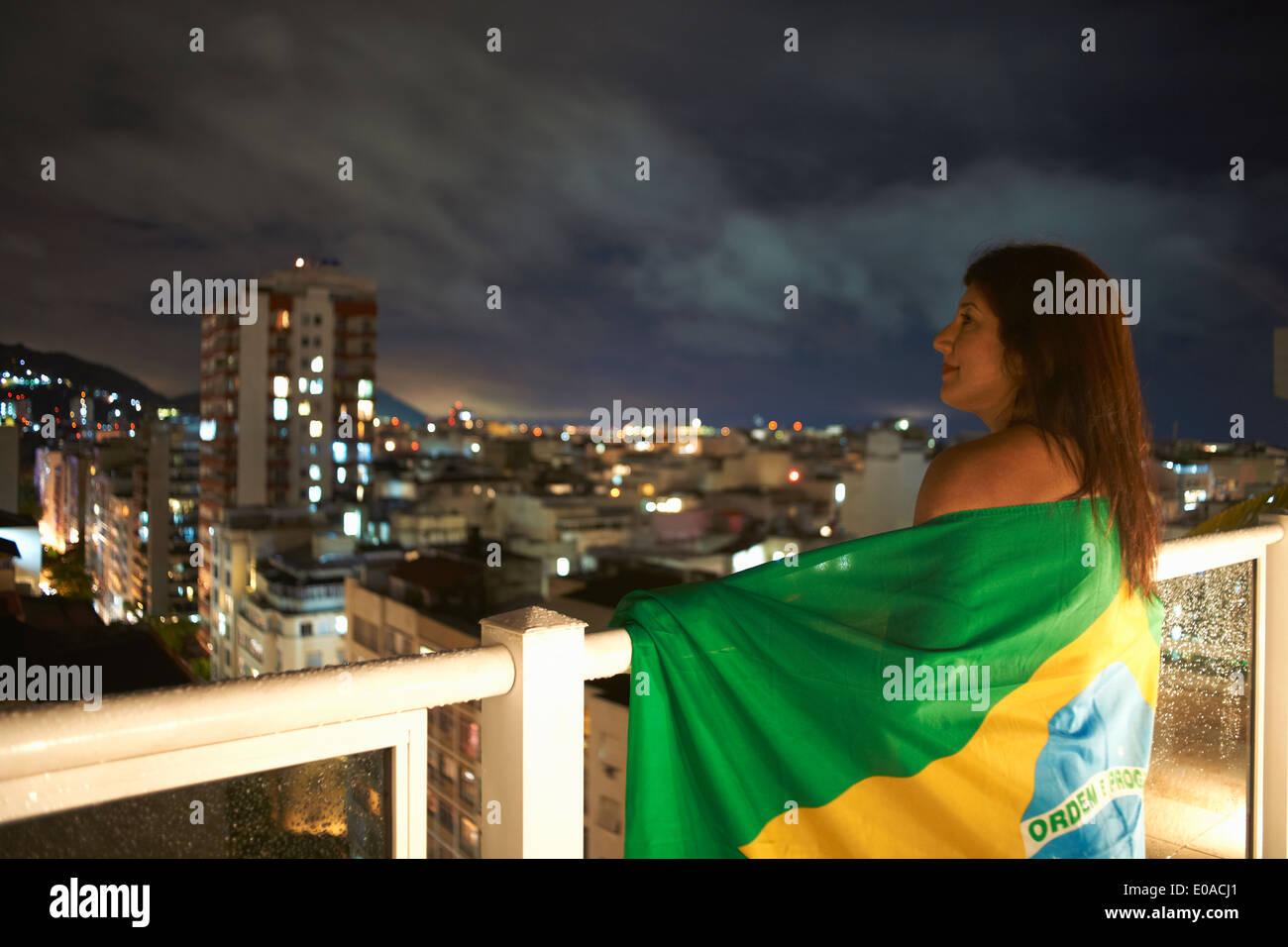 Mature woman gazing from balcony at night, Rio De Janeiro, Brazil - Stock Image
