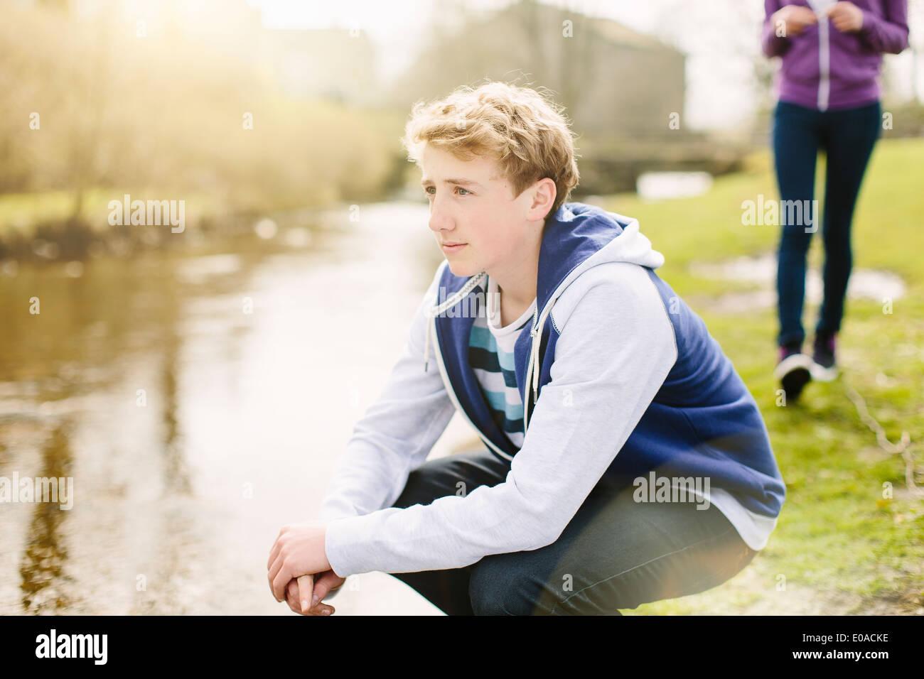 Unhappy teenage boy crouching on riverbank - Stock Image