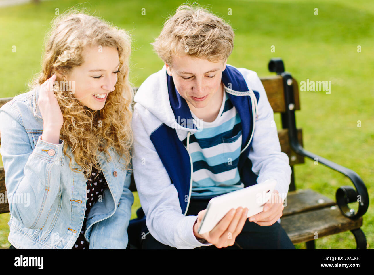 Teenage siblings looking at digital tablet on bench - Stock Image