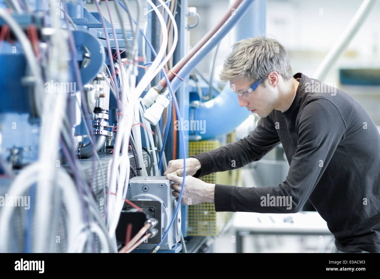 Mid adult male technician maintaining cables in engineering plant - Stock Image