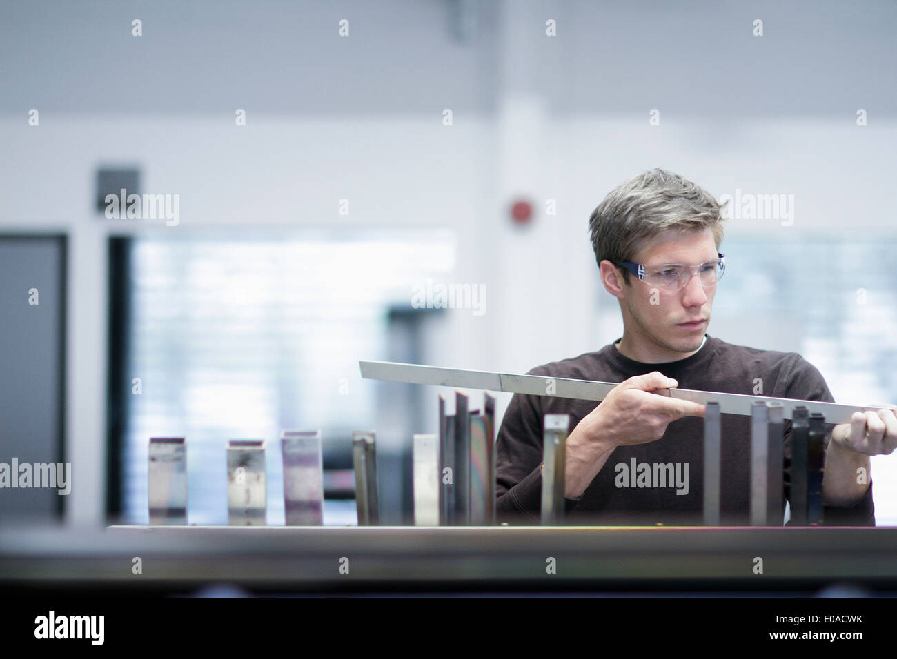 Mid adult male technician checking quality of products in engineering plant - Stock Image