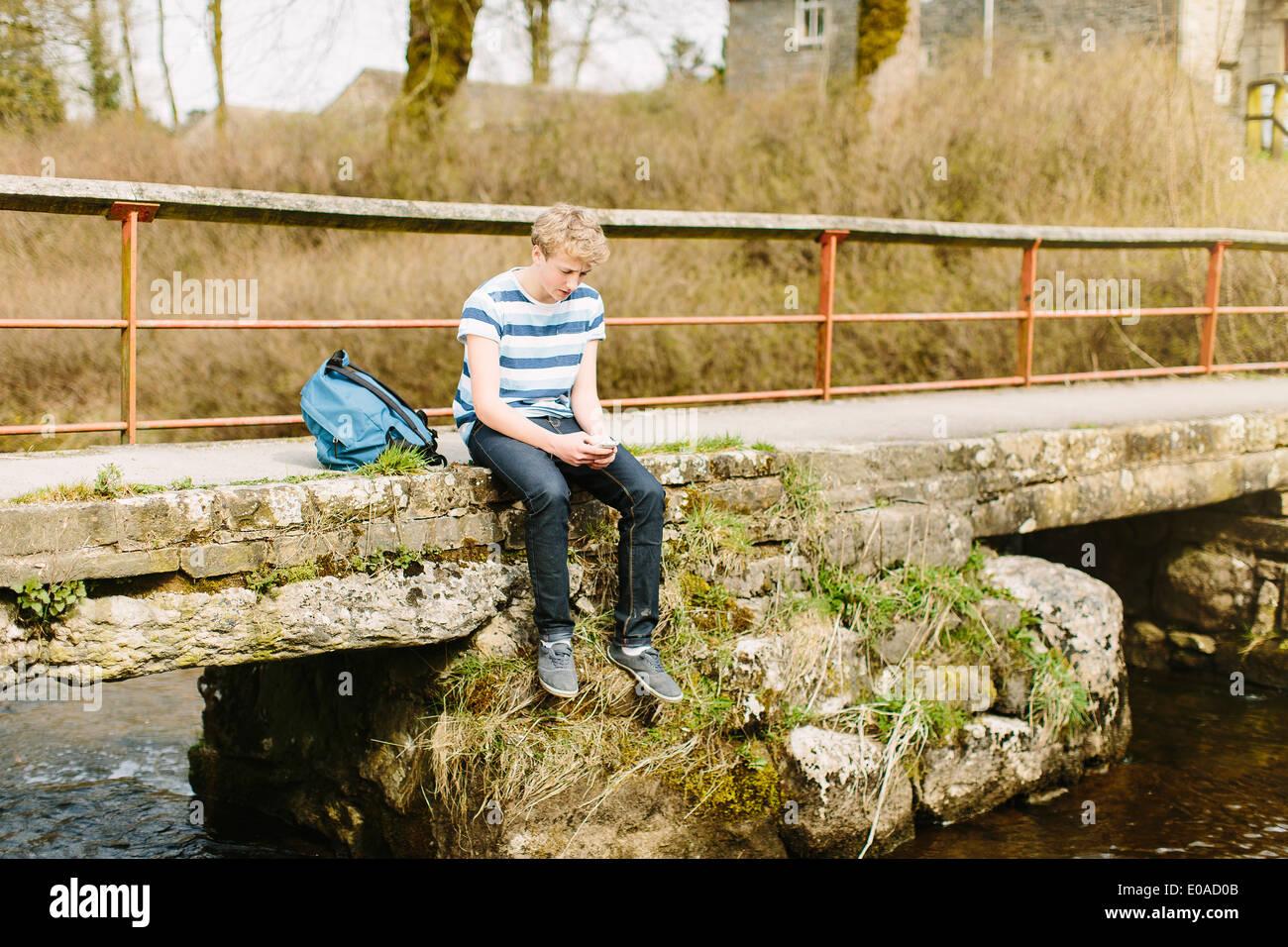 Unhappy teenage boy looking down from rural bridge - Stock Image