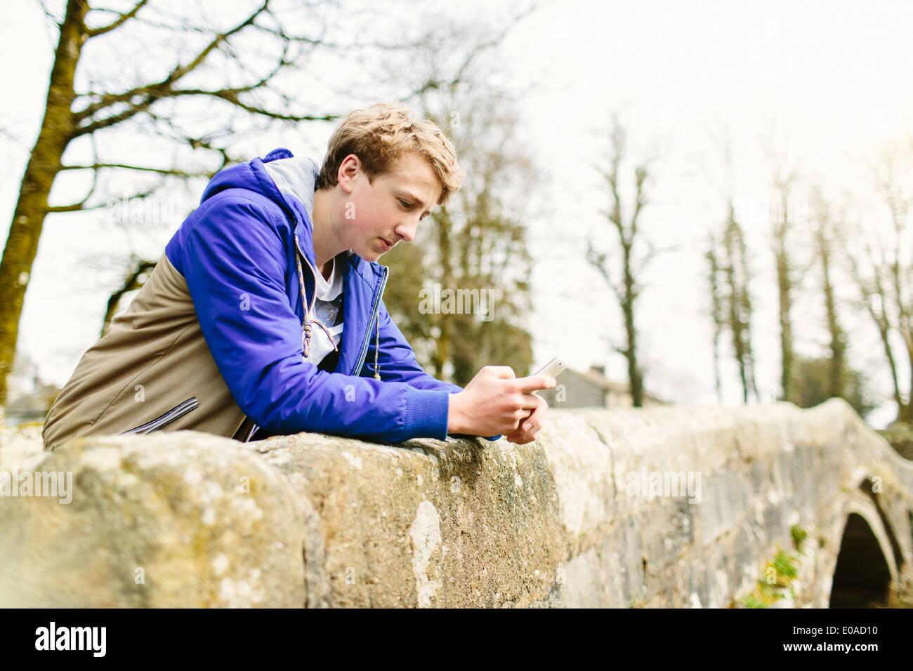 Unhappy teenage boy leaning over rural bridge - Stock Image