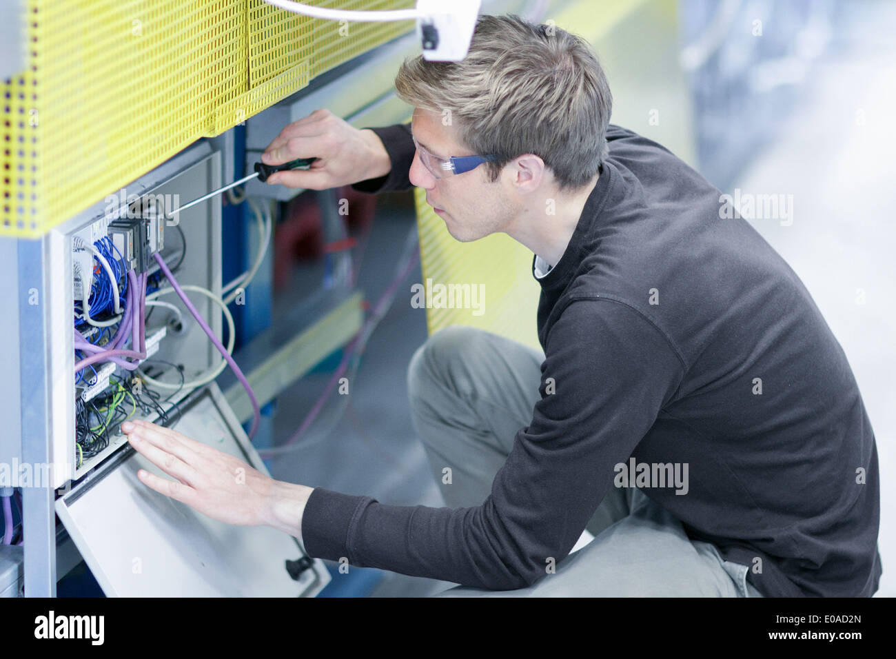 Mid adult male technician maintaining equipment in engineering plant - Stock Image
