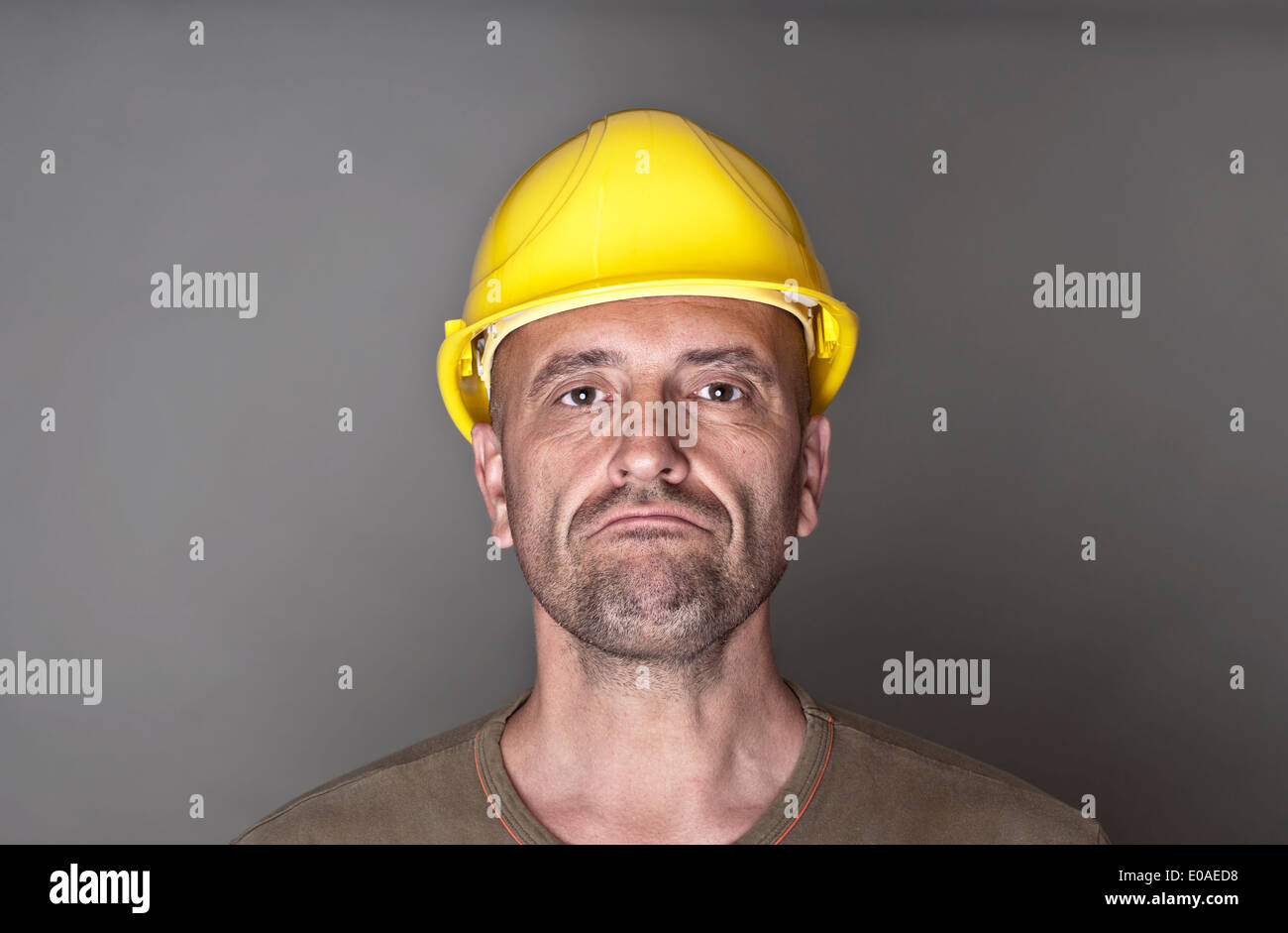 Portrait of an unhappy, skeptical worker with yellow hardhat - Stock Image